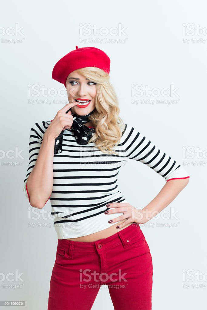Sensual blonde french woman wearing red beret Portrait of sensual beautiful blonde woman in french outfit, wearing a red beret, striped blouse and neckerchief, holding finger in mouth, looking away. Adult Stock Photo