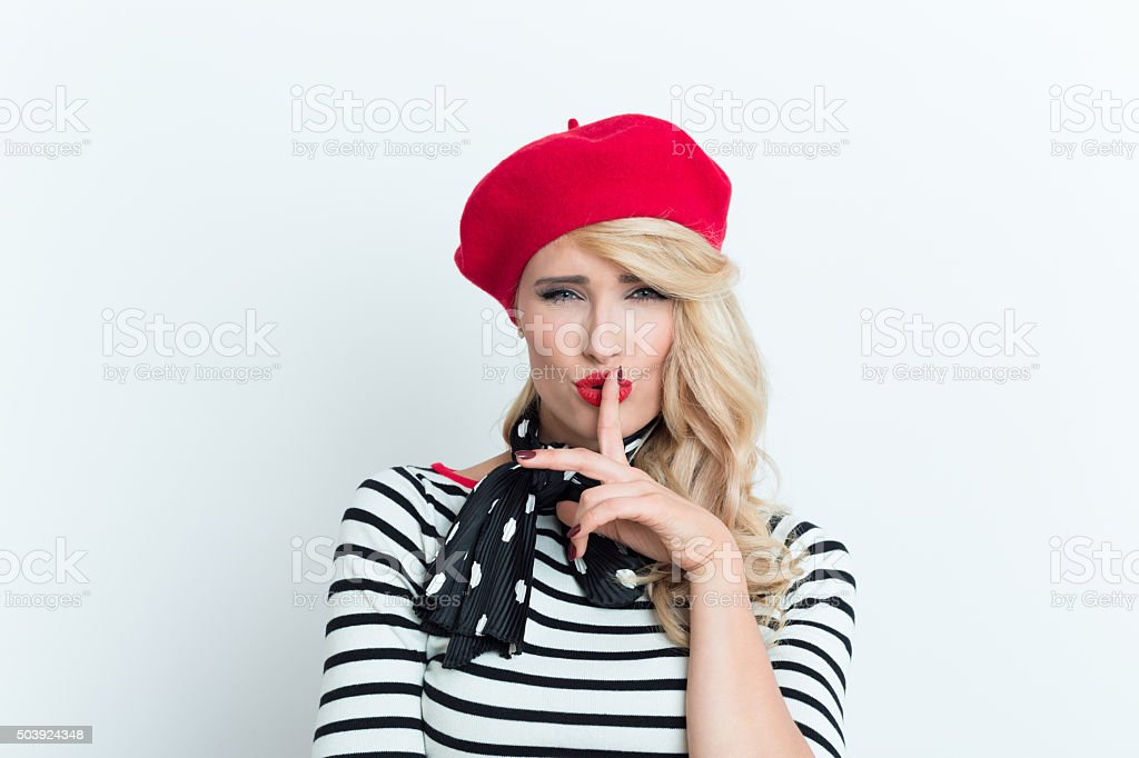 Sensual blonde french woman wearing red beret shushing Portrait of sensual blonde woman in french outfit, wearing a red beret, striped blouse and neckerchief, shushing. Adult Stock Photo