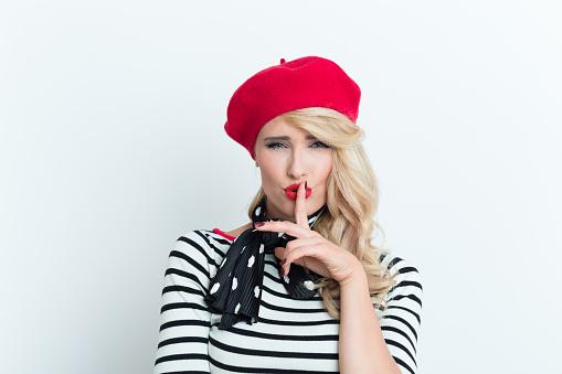 Sensual Blonde French Woman Wearing Red Beret Shushing Stock Photo - Download Image Now