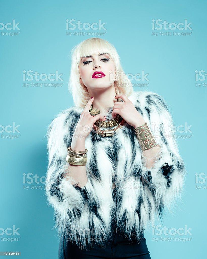 Sensual blonde woman wearing fur jacket and gold jewlery stock photo
