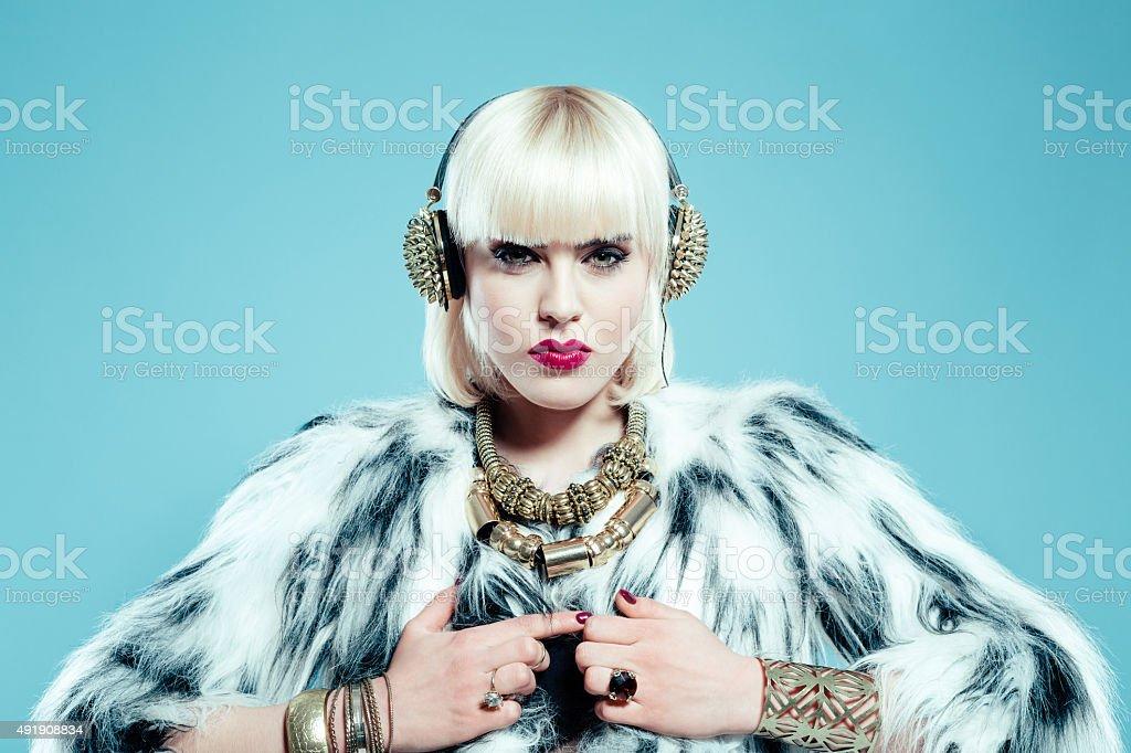 Sensual blonde woman wearing fur jacket, gold jewlery and headphone stock photo