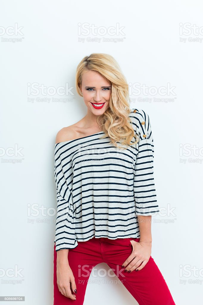 Sensual blonde woman wearing striped blouse and red trausers Portrait of sensual beautiful blonde woman wearing striped blouse and red trausers, laughing at camera. Adult Stock Photo