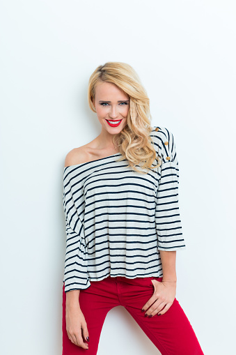 Sensual Blonde Woman Wearing Striped Blouse And Red Trausers Stock Photo - Download Image Now