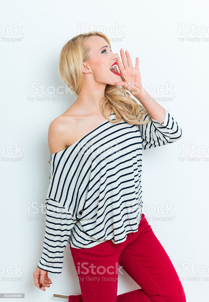 Sensual blonde woman wearing striped blouse and red trausers, shouting Portrait of excited beautiful blonde woman wearing striped blouse and red trausers, shouting. Adult Stock Photo