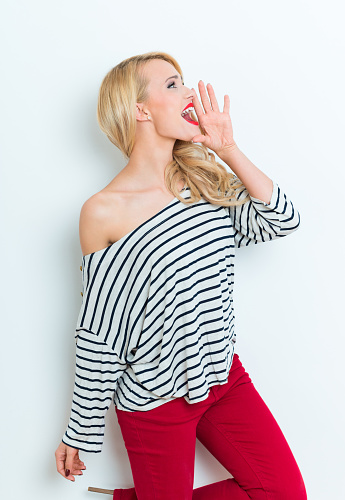 Sensual Blonde Woman Wearing Striped Blouse And Red Trausers Shouting Stock Photo - Download Image Now