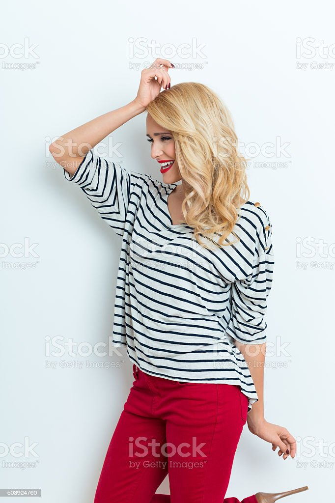 Sensual blonde woman wearing striped blouse Side view of sensual beautiful blonde woman wearing striped blouse and red trausers, looking away. Adult Stock Photo