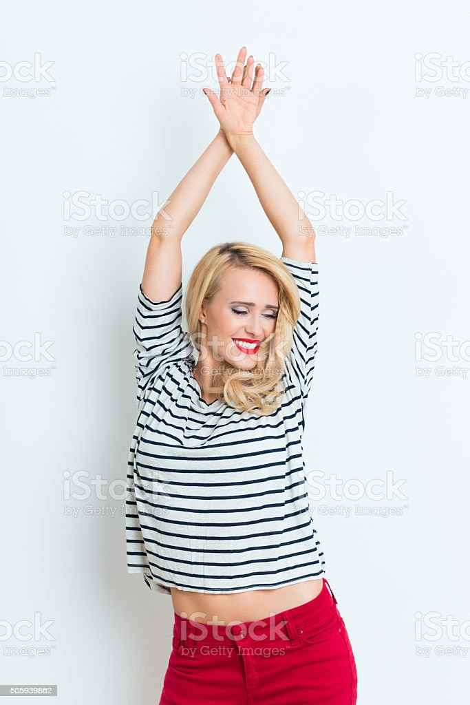 Sensual blonde woman wearing striped blouse, raised arms Portrait of sensual beautiful blonde woman wearing striped blouse and red trausers, raised her arms. Adult Stock Photo