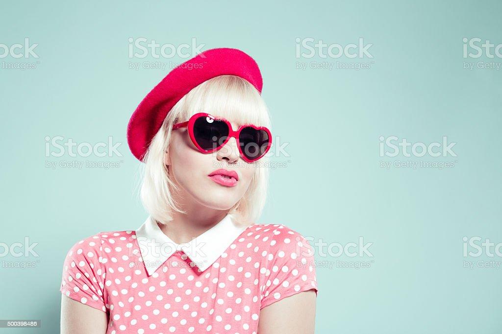 Sensual blonde young woman wearing heart shaped sunglasses stock photo