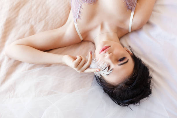 Sensual brunette beautiful woman lying on bed in white lingerie covering eye with feather stock photo