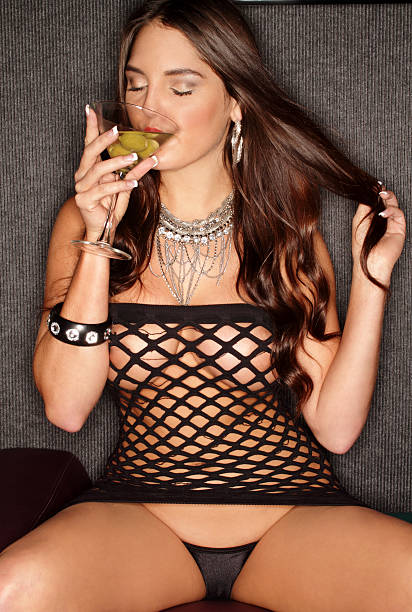 Sensual brunette drinking martini with many olives stock photo