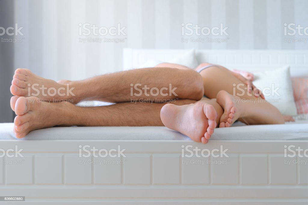 Sensual couple in bedroom, unrecognisable couple spooning in bed stock photo