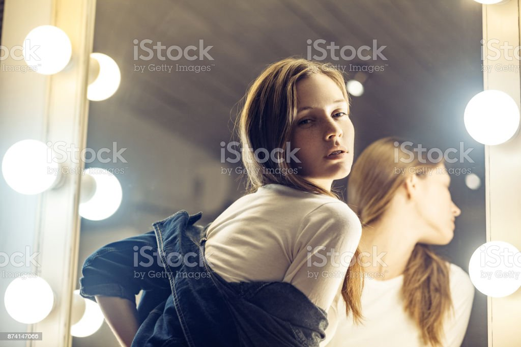 Sensual cute girl in blue jacket ready for romantic date. Adorable young woman posing near the makeup mirror in her room with sensual look. stock photo