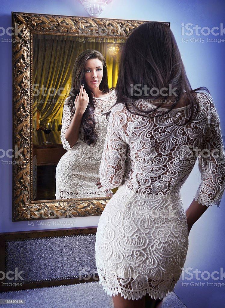 Sinnliche elegante junge Frau im weißen Kleid auf der Suche in Spiegel – Foto