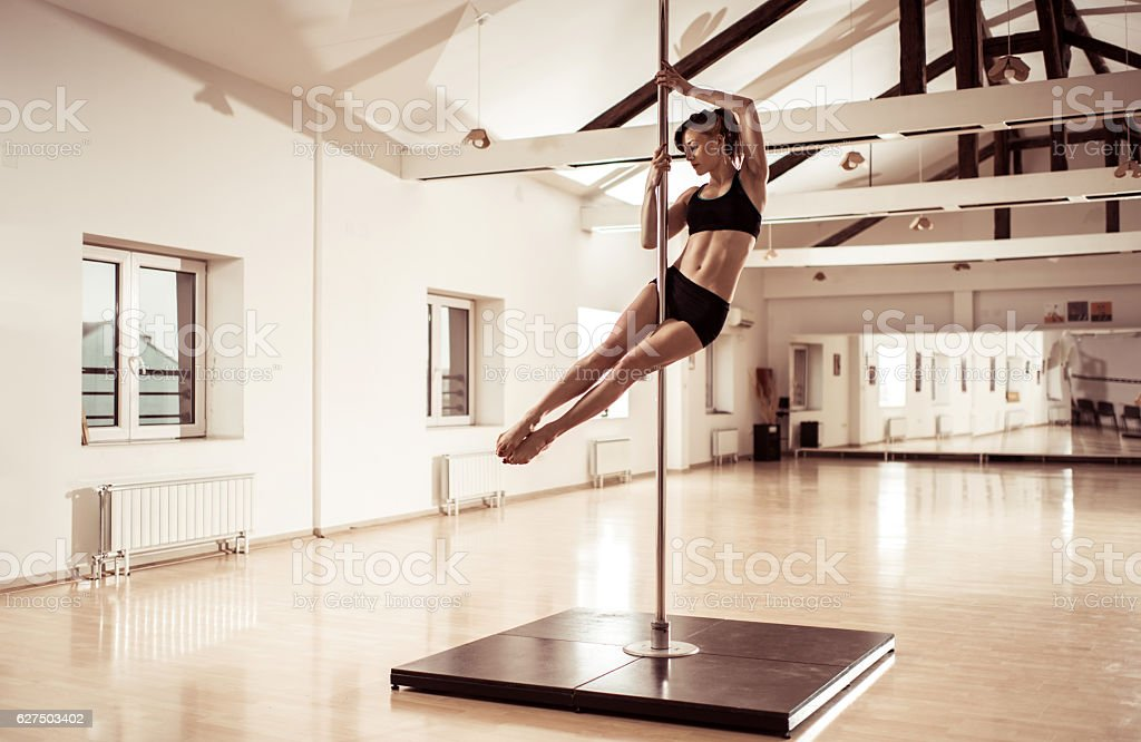 Sensual female dancer dancing on a pole in a studio. stock photo