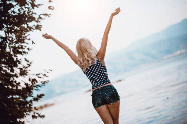 sensual female enjoying summer and lake vacation - jean shorts stock photos and pictures