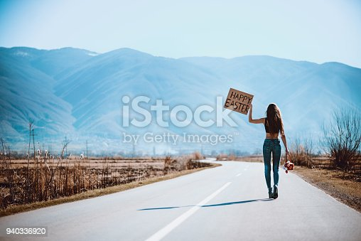 istock Sensual Female on Empty Road Hitchhiking with Raised Happy Easter Board 940336920