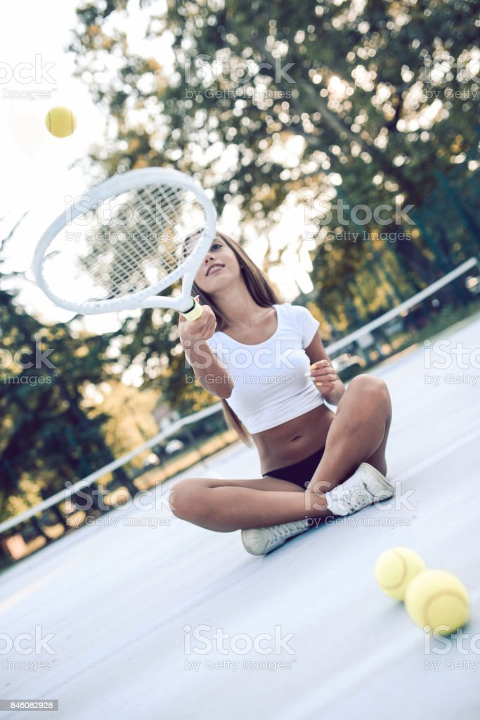 Sensual Female Sitting on Tennis Court Juggling with Racket And Ball stock photo