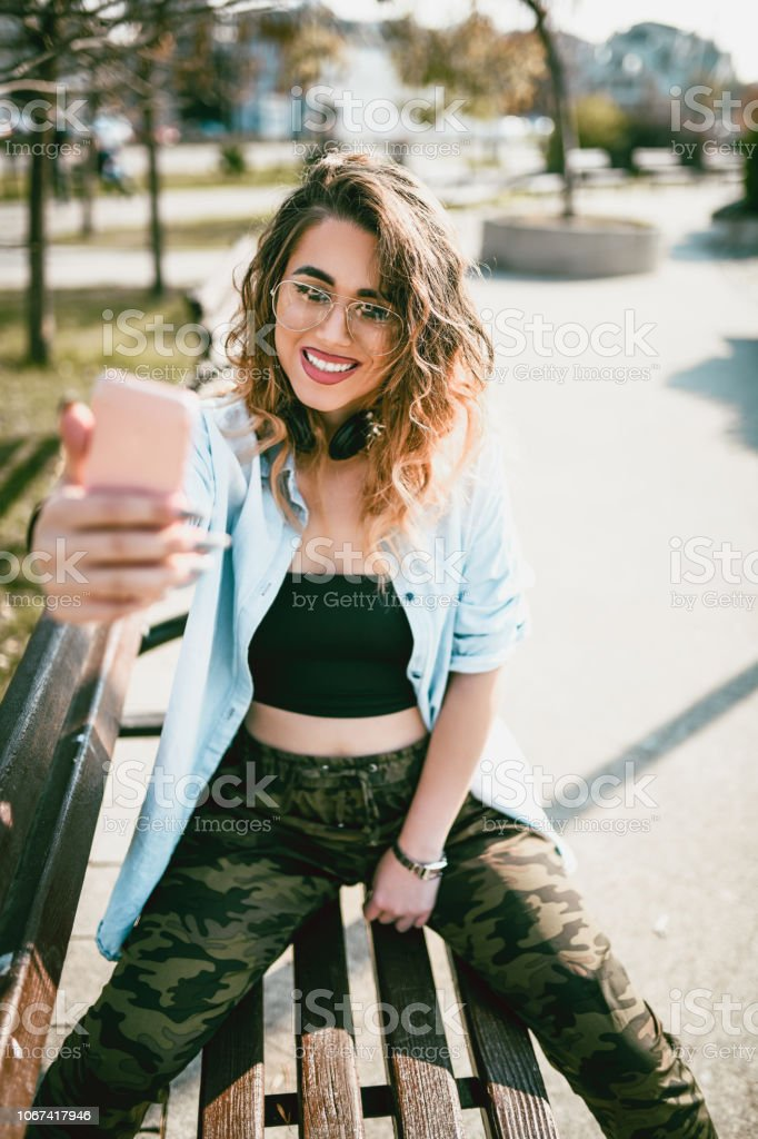 Sensual Female Taking a Autumn Selfie On a Park Bench stock photo