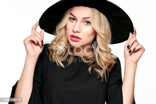 512061362 istock photo Sensual Halloween Witch Studio Portrait. Attractive young woman dressed in witch halloween costume isolated over white background. 1050396120