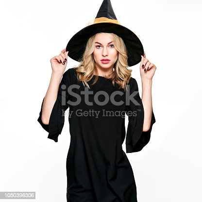 512061362 istock photo Sensual Halloween Witch Studio Portrait. Attractive young woman dressed in witch halloween costume isolated over white background. 1050396306