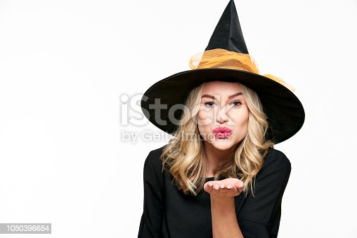 512061362 istock photo Sensual Halloween Witch Studio Portrait. Attractive young woman dressed in witch halloween costume isolated over white background blowing a kiss towards camera. 1050396654