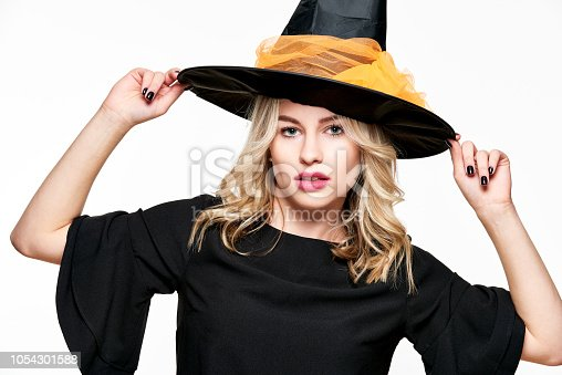 512061362 istock photo Sensual Halloween Witch Studio Portrait. Attractive young woman dressed in witch halloween costume isolated over white background. 1054301588