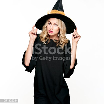 512061362 istock photo Sensual Halloween Witch Studio Portrait. Attractive young woman dressed in witch halloween costume isolated over white background. 1054302294