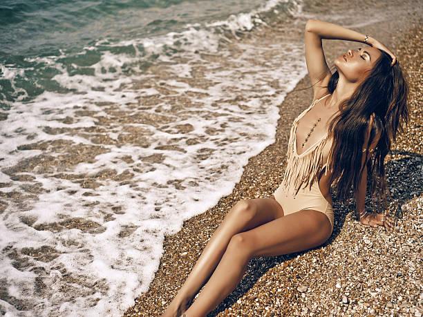 sinnliche dame am strand - haare ohne lockenstab wellen stock-fotos und bilder