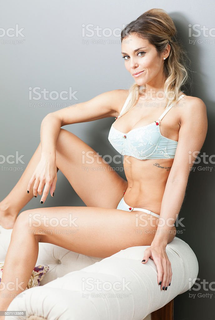 Sensual latin blond woman in lingerie lying on a sofa - Stock image .