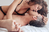Young couple being intimate kissing on bed. Sensual lovers making love in bedroom.