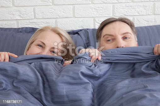 istock Sensual mature couple together in bed. Happy couple in bedroom enjoying sensual foreplay. 1168736171