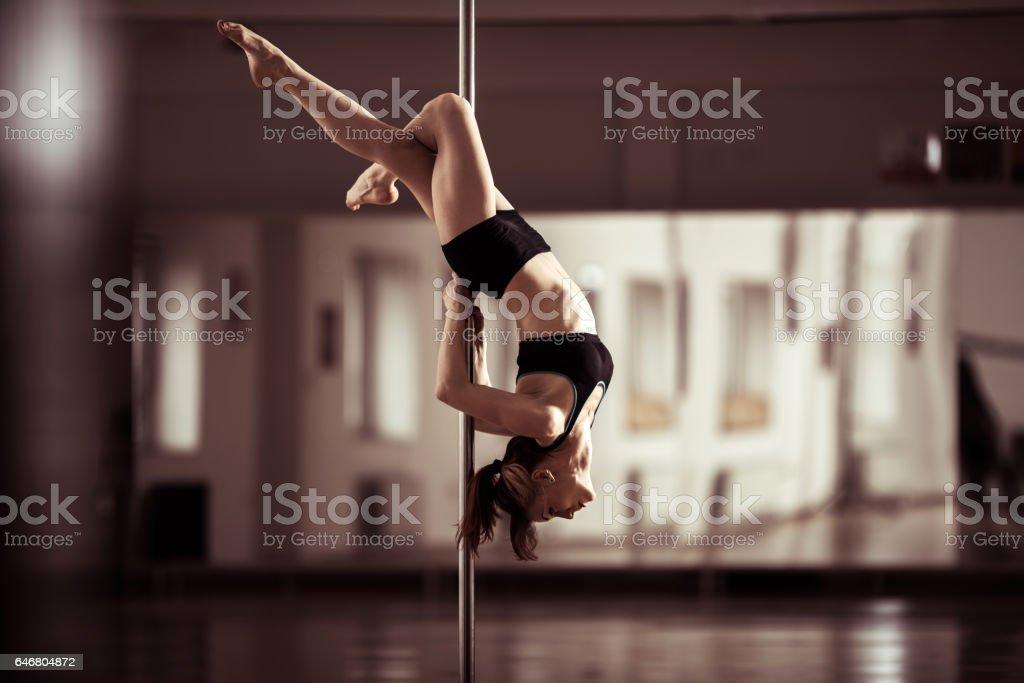 Sensual pole dancer dancing in a studio. stock photo
