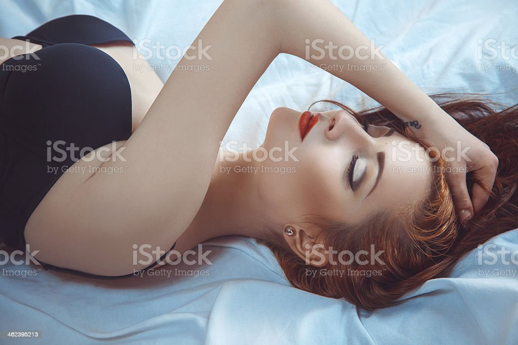 Sensual red hair woman lying in bed stock photo