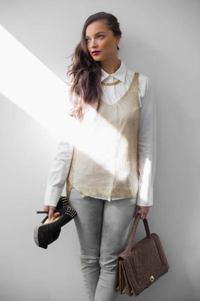sinnliche trendige frau mit high heels und handtasche - pflaumen jeans stock-fotos und bilder