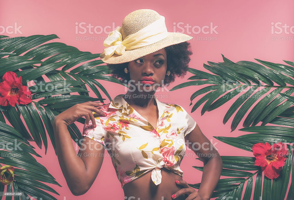 Sensual Tropical Afro American Pin-up with Hat Between Palm Leaves. stock photo