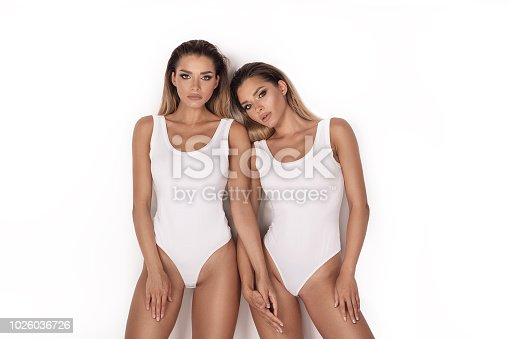 Sensual twins women with fit slim bodies posing on white studio background. Girls in glamour makeup.