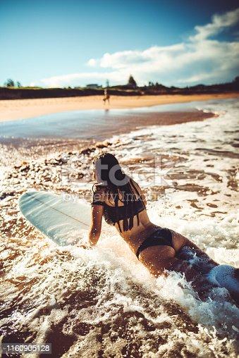 sensual woman splashing on the sea with surfboard