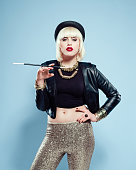 Portrait of posh blonde young woman wearing black leather jacket, gold trousers and jewlery, bowler hat, holding cigarette holder in hand, looking at camera. Studio shot, blue background.
