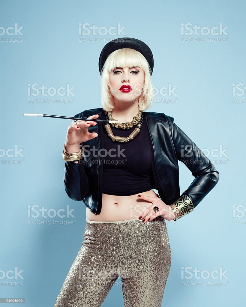 Sensual woman wearing leather jacket, gold trousers and bowler hat stock photo