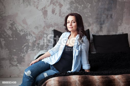 istock Sensual woman with dark hair in blue shirt and jeans sitting on a bed at home. Loft style interior 666693498