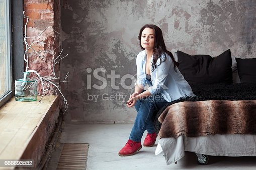 istock Sensual woman with dark hair in blue shirt and jeans sitting on a bed at home. Loft style interior 666693532