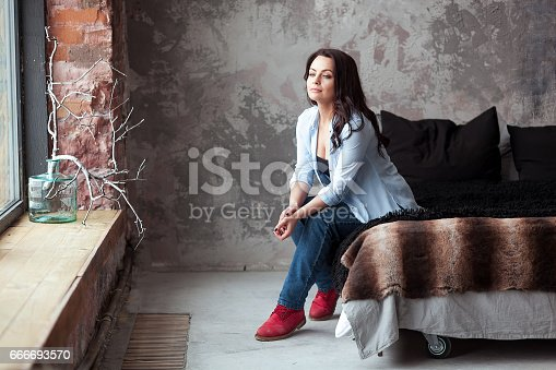 istock Sensual woman with dark hair in blue shirt and jeans sitting on a bed at home. Loft style interior 666693570