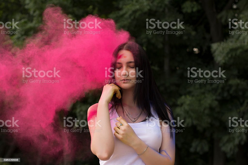 Sensual woman with pink powder falls down on her royalty-free stock photo