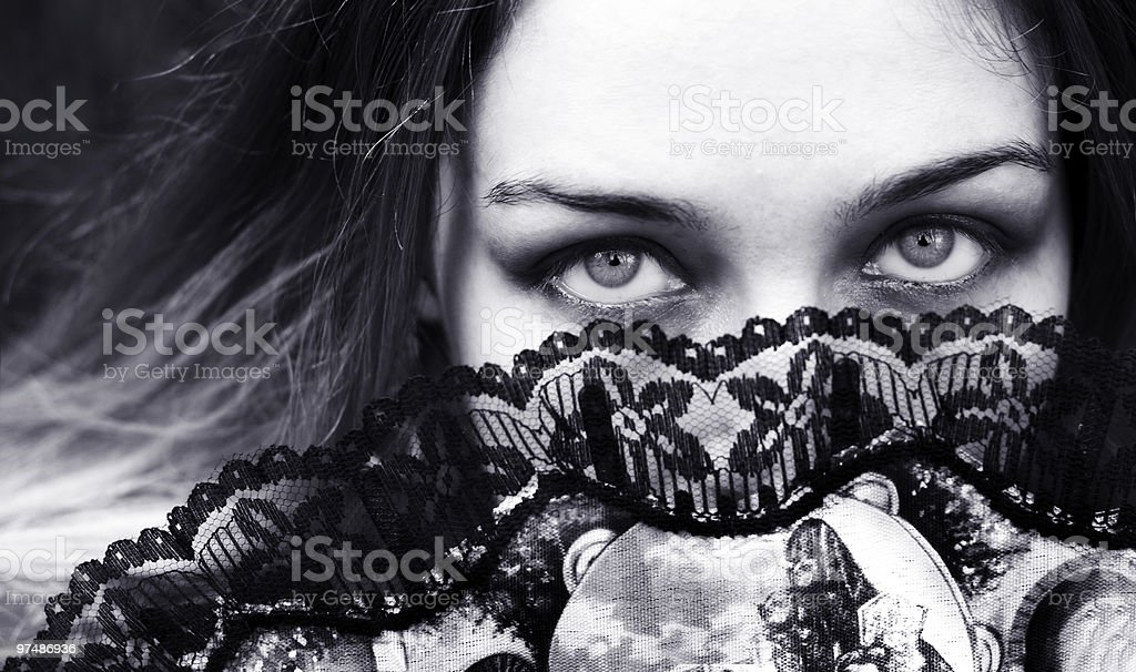 Sensual woman with seductive eyes behind fan royalty-free stock photo
