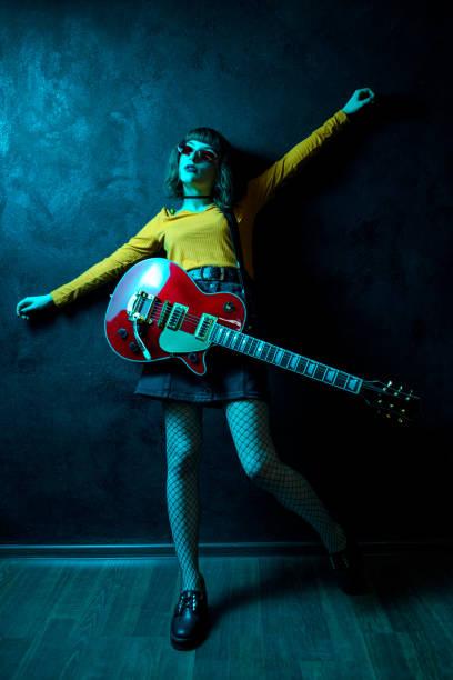 sinnlich junge hipster-frau mit lockigen haaren mit roter gitarre in neonlicht. rockmusiker spielt elektrische gitarre. 90er-jahre-konzept. - bands der 90er stock-fotos und bilder