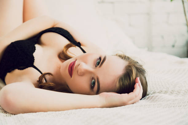 Sensual young woman in black lace lingerie body lying in white bed stock photo
