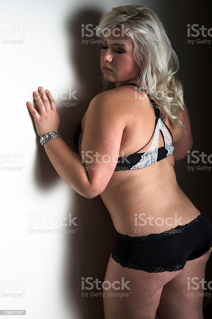 43ed3a7bd15ad8 Sinnliche Junge Frau in schwarzen Dessous auf Wand gelehnt Lizenzfreies  stock-foto