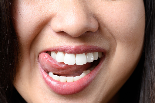 Sensual Young Woman Licking Her Teeth Stock Photo