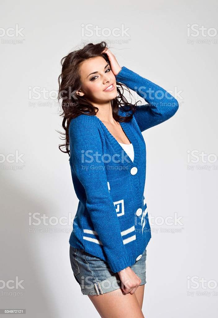 Sensual young woman Portrait of sensual young woman wearing blue cardigan and shorts, looking at camera. Studio shot, white background. 20-24 Years Stock Photo