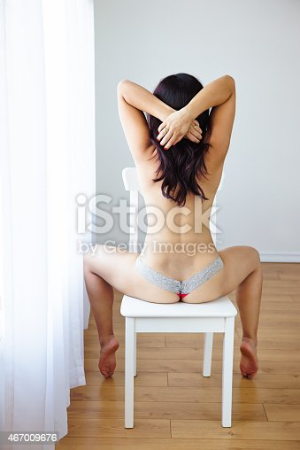istock Sensual young woman posing in panties sitting on chair 467009676